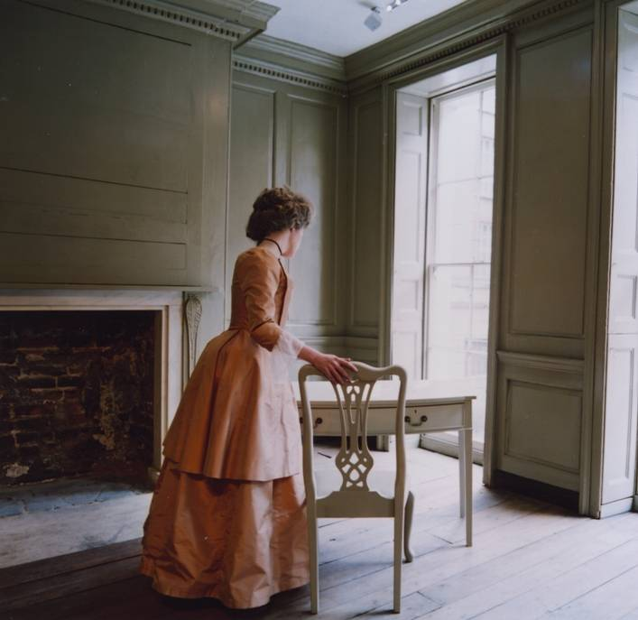 Polly, in a Georgian silk dress, leans over Franklin's desk