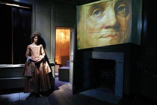 Polly, in a Georgian silk dress, beside projection on the wall