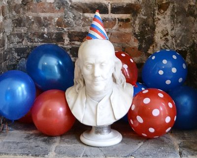 Benjamin Franklin bust with party hat on and red and blue balloons