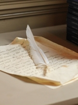 Feather quill and paper on desk