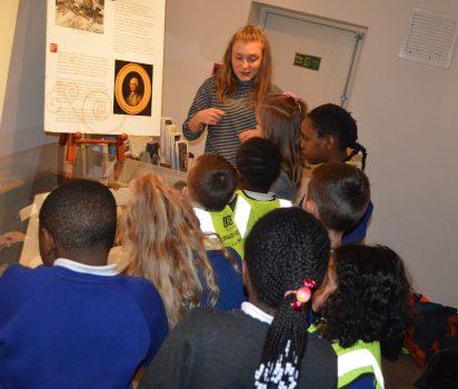 Volunteer showing children the bones in the basement
