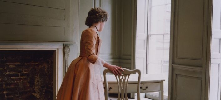 Polly, a woman in a Georgian silk dress, leaning over the desk in Franklin's parlour