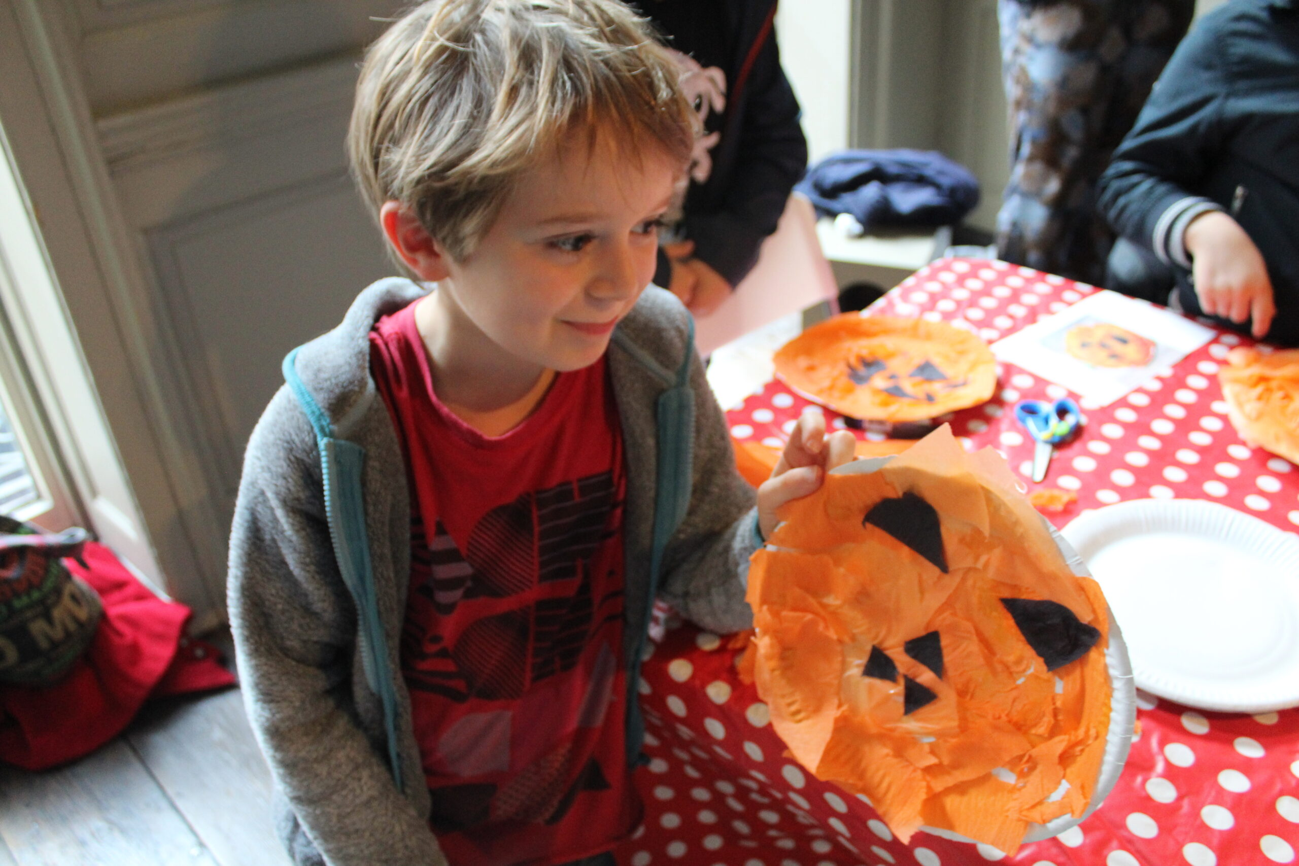 A young boy holds up the pumpkin face he has made using a paper plate and coloured paper.