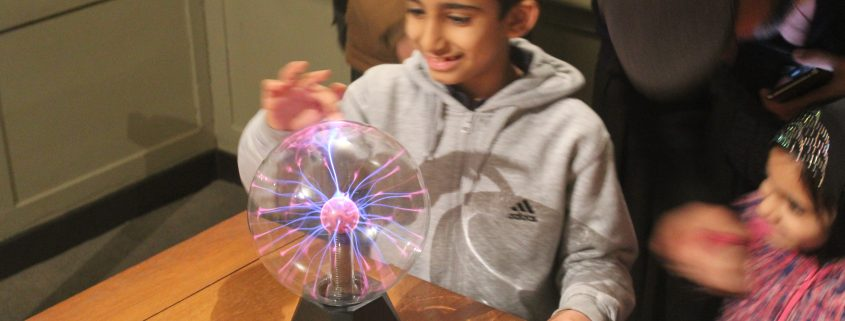 Student playing with a plasma ball