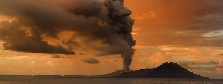 Volcano eruption with plume of smoke rising above an island and the sea