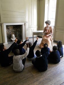 Polly teaches children about the quill. Kids hold their hands up to ask a question