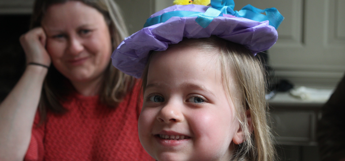 Child smiling at the camera while wearing a homemade purple and blue Easter bonnet with two fluffy yellow chickens on and a ribbon