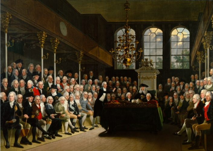 Painting of William Pitt addressing the House of Commons on the outbreak of war with Austria in 1793. He stands in the centre speaking to a crowded room of richly dressed white men in Georgian white powdered wigs. The room is expensively decorated with gold columns and chandelier.