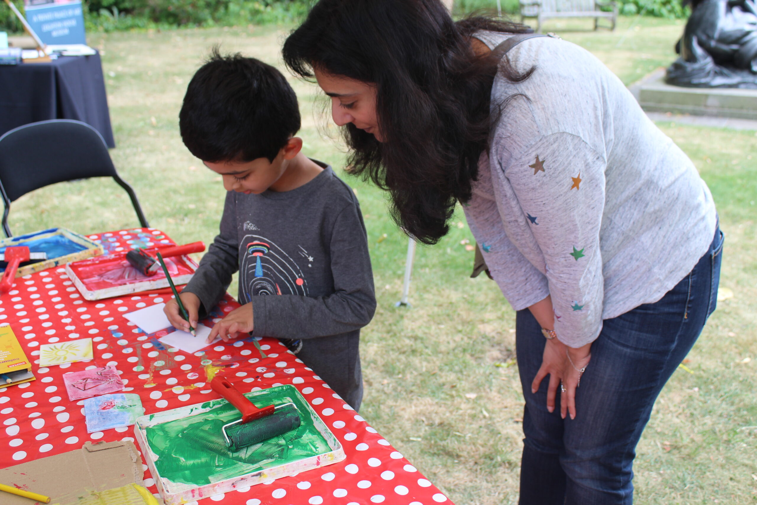 A young boy with his mother completing a lino print