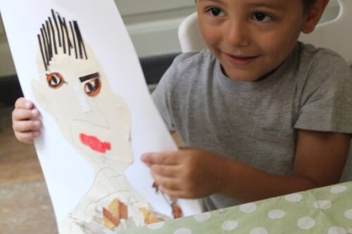 A young boy holds up a collage self-portrait